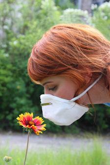 smelling flower wearing mask